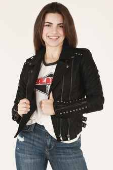 front of jacket in black shows silver zipper detailing with classic moto fit, studs at bottom arm length and shoulders paired with rocker tee and blue denim.