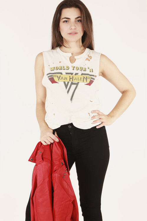front of shirt features Van Halen vintage logo with purposed holes at top shoulder while model holds red leather jacket paired with black jeans.