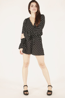 full body front image shows long sleeve shorts romper paired with black platforms