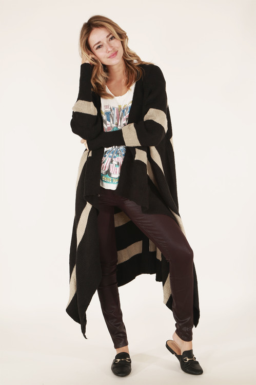Front full view shows sweater in black and taupe stripes paired with band tee and wine-colored wax pants