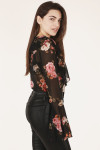side view shows long sleeve and semi-sheer material with black jeans