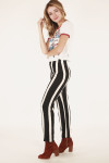 side full body view shows tee paired with black and white pants and maroon booties