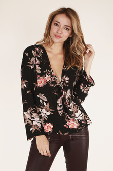 front close up view shows pattern with black background and pink, white and tan flowers all over. Tie at front V-neckline