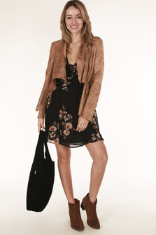full front view shows dress in black background with cream and neutral color flowers all over paired with black home bag and faux suede brown jacket.