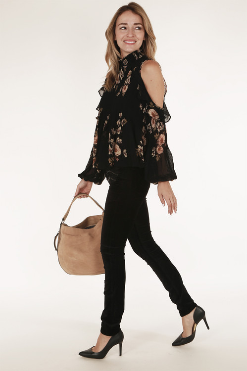 full view shows side of blouse with cold shoulder paired with black jeans and tan purse