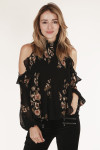 close up view of front shows high neck with ruffle detail and print in black background with tan flowers all over