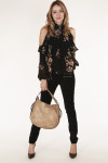 full front view shows pants paired with cold shoulder black floral blouse with tan purse