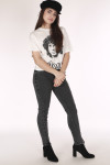 full body front shows model in black hat with white Jim Morrison tee and side lace up grey jeans.