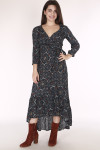 front of dress shows 3/4 length sleeves with v-neck, wrap front with higher front hemline. Print has navy background with red, yellow & white flowers all over. paired with red suede boots