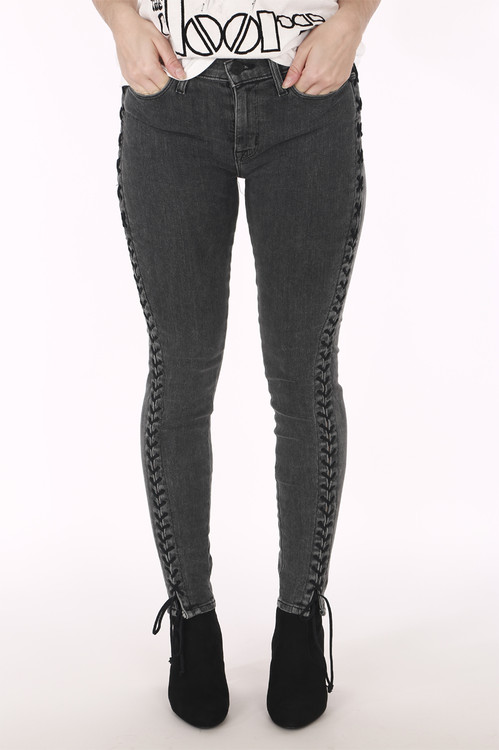 close up shows super skinny leg in dark grey with black lace up detailing on side