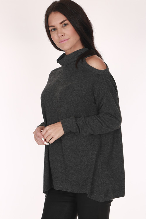 side view shows cold shoulder cut out with turtleneck top and wide fit