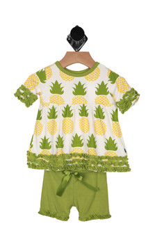 front shows babydoll style top with pineapples printed all over with ruffle detailing at all hems. with matching green shorts that have ribbon tie at elastic band and ruffle detail at bottom hem.