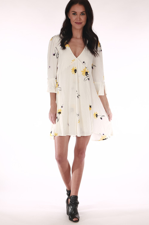 front shows mini length with 3/4 sleeve arms and wrap front. Print is cream background with yellow daisies all over