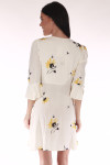 back shows mini length with 3/4 sleeve arms and wrap front. Print is cream background with yellow daisies all over