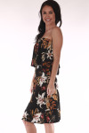 side shows strapless dress with black background and orange, red and green flowers all over with ruffle overlay at top and length that hits right at knees.