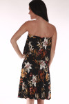 back shows strapless dress with black background and orange, red and green flowers all over with ruffle overlay at top and length that hits right at knees.