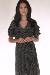 front shows black and white polka dot material with ruffle detailing at top and wrap front closure
