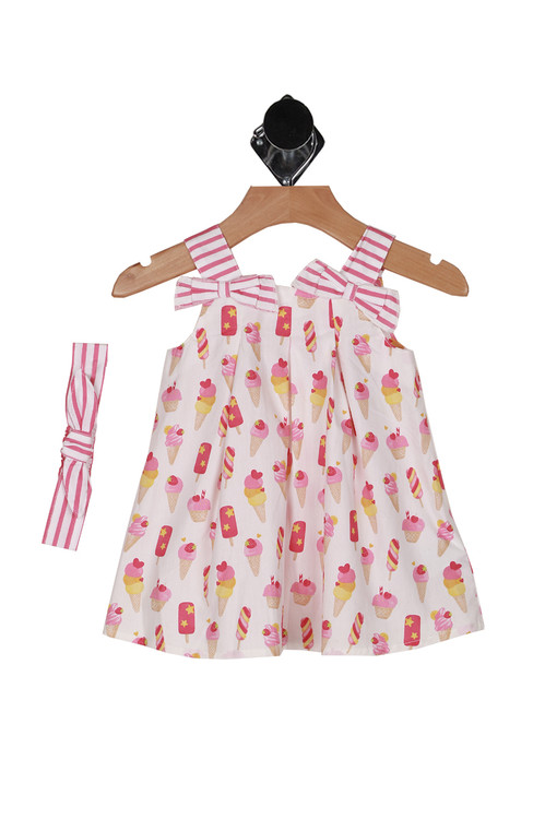 print of dress shows pink and white striped straps with all over pink and orange ice cream print. Comes with matching pink and white striped headband