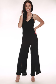front shows Black Swan jumpsuit featuring a culotte wide length bottom with with side slits and brass circular cut outs at top and adjustable straps.