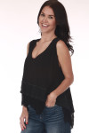 Side shows black tank top with hi-lo hemline, tiered ruffle hemline, light semi-sheer material, and v-neckline. Shown worn with Blue jeans.