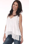 Side shows white tank top with hi-lo hemline, tiered ruffle hemline, light semi-sheer material, and v-neckline. Shown worn with Blue jeans.
