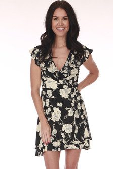 Front shows Black and ivory flower print mini dress with ruffled v shape neckline and short ruffled shoulders.