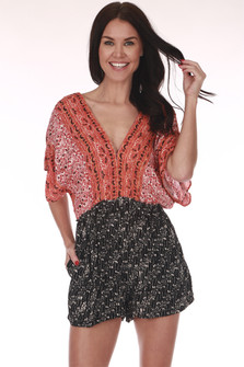 Front: Red, black, and ivory multi patterned shorts romper with  v shape neck line.