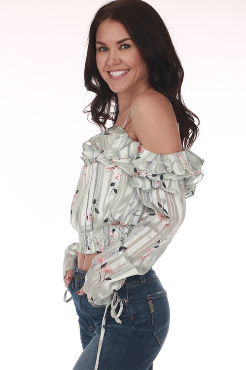 side shows off the shoulder sleeve with ruffle layer at top in a mint color and flowers all over. features long sleeves and cropped hem with elastic band at bottom
