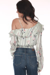 back  shows off the shoulder sleeve with ruffle layer at top in a mint color and flowers all over. features long sleeves and cropped hem with elastic band at bottom