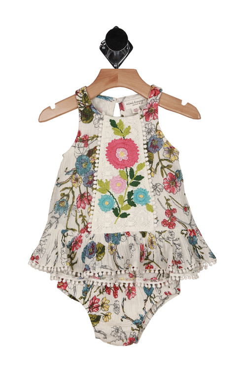 Front shows floral print all over in greens, blues, pinks and a cream background. Shows matching bloomers