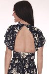 Back shows Black and ivory multi flower patterned crop top with open back and mid arm length shoulders.