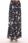 Back shows multi floral patterned black and white flow pants with high slits at front.