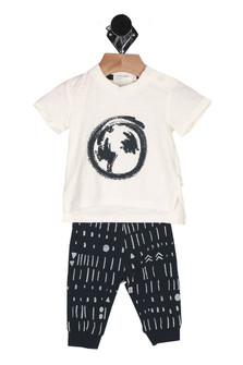 Front: Two piece white tee top with black outline earth symbol and multi patterned long pants.