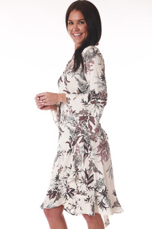 side view shows bell long sleeves with all over floral print white cream background and light blue and dark purple flowers.