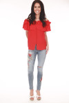 Full front shows red ruffled off shoulder blouse with button up front shown paired with ankle length blue denim skinny jeans with red flower design on left leg.