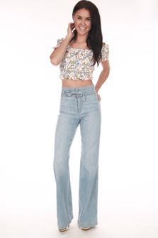 full front shows light blue denim jeans with belted top, no front pockets, and super wide flare bottoms paired with floral crop top.