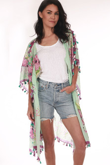 Front shows Knee length teal and flower printed kimono with tasseled sleeves and slit shoulders. Shown worn with light mid thigh  denim jeans and a white tank.