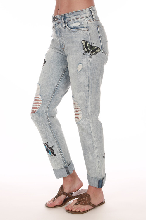 Side shows light blue denim crop relaxed straight ripped jeans with monarch butterflies. Shown worn with sandals.