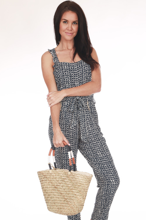 Front shows straw tote bag with short hand held white, black, and rust striped straps.
