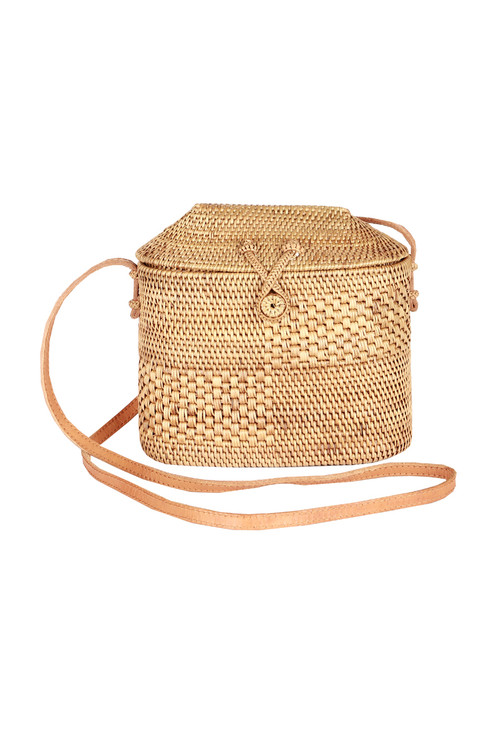 Front shows fold over rattan cross body bag with long strap and snap top.