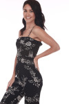 Front side shows black jumper suit with white floral print pattern, spaghetti straps. and small v-shape top.