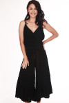 Front shows black wide flare leg cropped jumpsuit with spaghetti straps, v-shape neckline, and waste tie.  Shown worn with sandals.