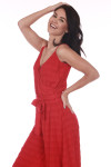 Side shows red wide flare leg cropped jumpsuit with spaghetti straps, v-shape neckline, and waste tie.