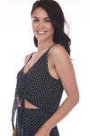 side shows black and white polka dot button down spaghetti strap crop tank with buttons and bottom tie. Paired with matching flare pants that go all the way to the floor.