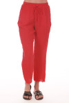 Front shows red gauze pants with pockets, raw hem, and string waste tie. Pants fit to ankles.