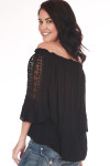 Back shows black off-shoulder classy blouse with lace crochet designs down the arms and plain black color at back.