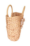 Side shows tightly knitted natural hand held straw bag with round levers. Straw tree-like design on front.