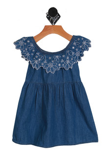 Blue denim material dress with ruffled white flower stitches at the top of shoulders.