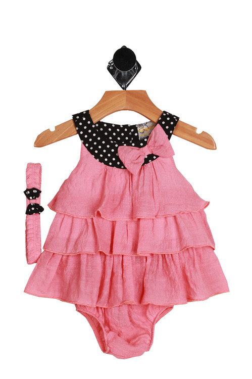 Front:  Top shows black and white polkadot band at chest and pink ruffled layered bottom. Comes with matching bloomers and headband.