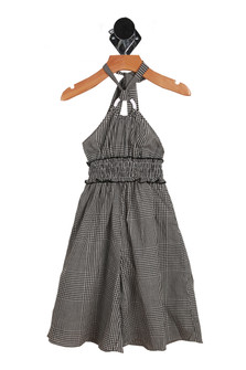 """Front"""" Criss-cross summer halter dress with round connecting piece in the middle of chest. Black and white checker design."""